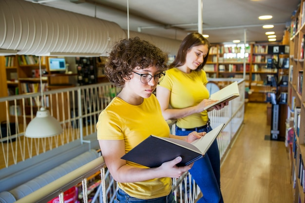 Teen girls reading books in library