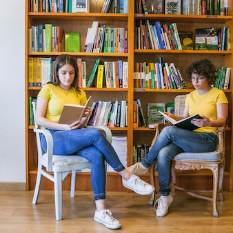 Teen girls reading on chairs near bookcase
