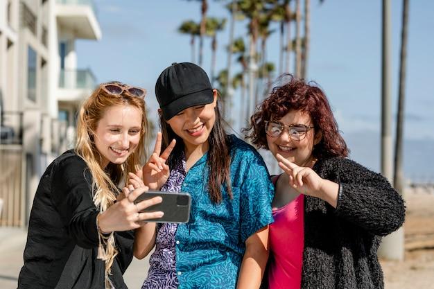 셀카를 찍고 있는 십대 소녀들, 로스앤젤레스 베니스 해변에서 함께 여름을 즐기고 있습니다.