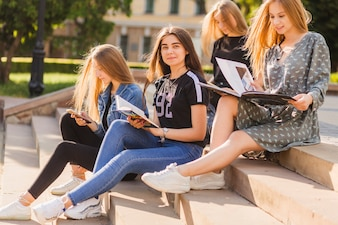 Teen girls with book sitting among friends