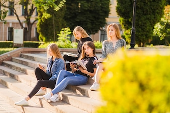 Teen girls with books and smartphone relaxing on steps