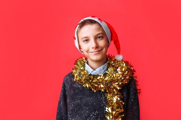 Подросток в новогодней шапке и с мишурой на шее улыбается на красной стене