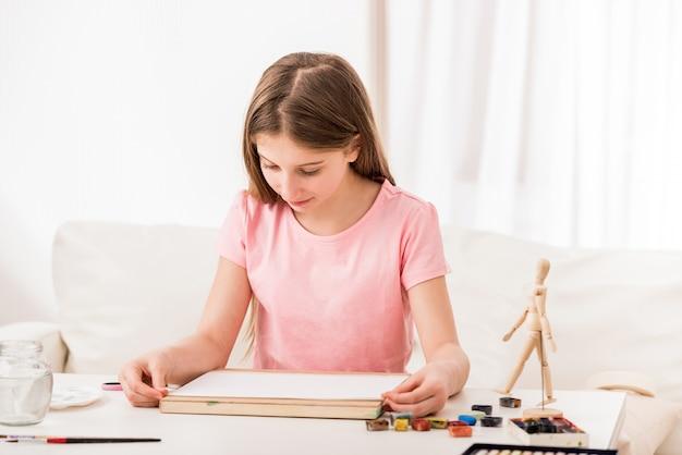 ティーンは何かを描くために紙を修正しています