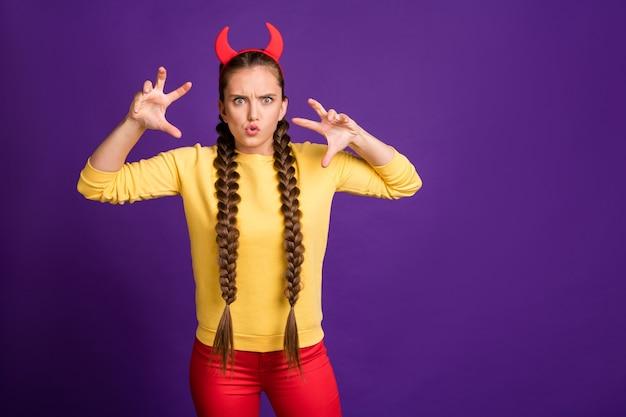 헬로윈 파티에서 사탄 역할을하는 십대 아가씨 무서운 표현 착용 뿔 머리띠 캐주얼 노란색 풀오버 빨간 바지 절연 보라색 컬러 벽