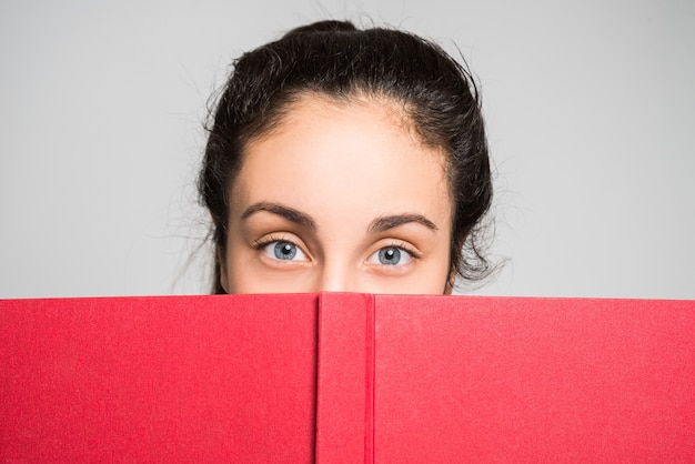 Teen looking from behind a book