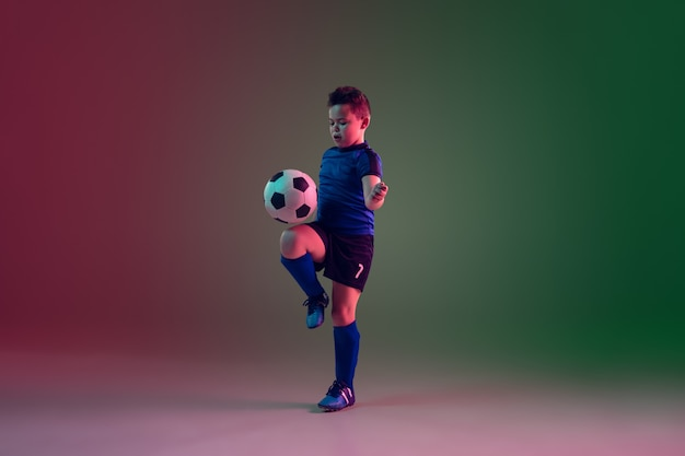 Teen male football or soccer player, boy on gradient background in neon light - motion, action, activity concept