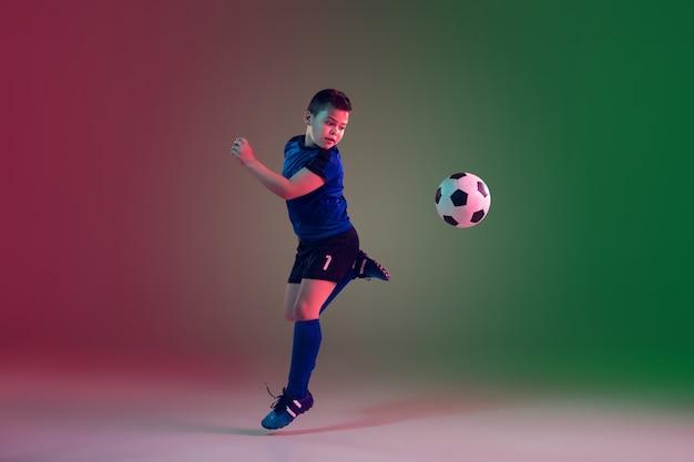 ネオンの光のグラデーションの壁に10代の男性サッカー選手