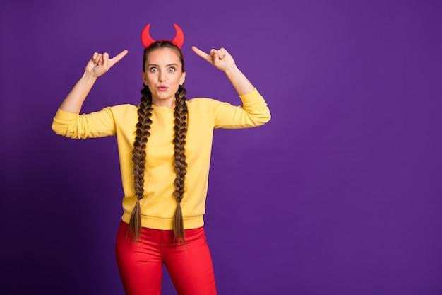 뿔 머리띠에 손가락을 나타내는 십대 모델 아가씨 캐주얼 노란색 풀오버 빨간 바지 절연 보라색 컬러 벽을 착용