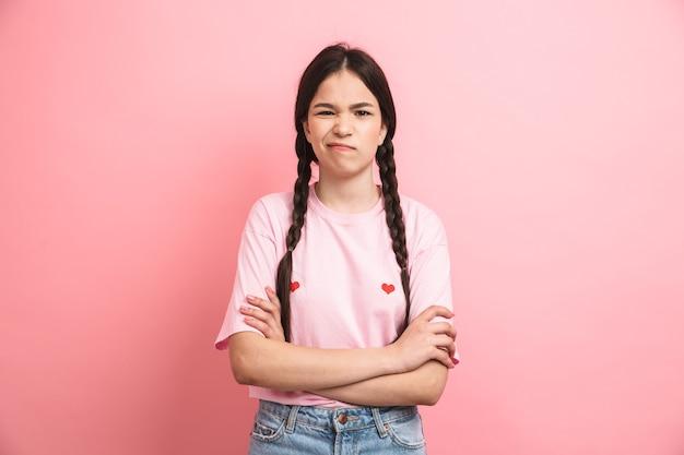 ピンクの壁の上に孤立して腕を組んで正面を見て2つの三つ編みを持つ10代の憤慨した女の子