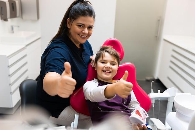 Пациент-подросток и стоматолог показывают палец вверх