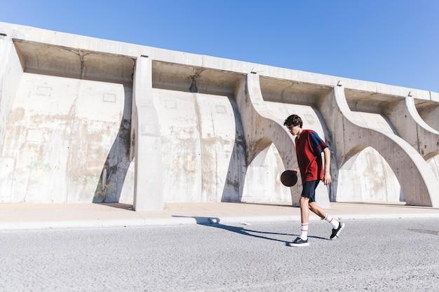 Teen practicing basketball near surrounding wall