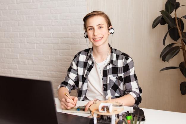 Подросток занимается программированием и строит научную робототехнику на своем ноутбуке дома во время изоляции от пандемии covid-19