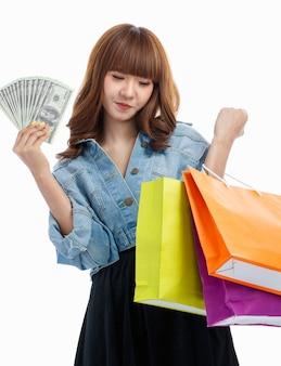 手に広げてカラフルな買い物袋を持っているアメリカの紙幣を持っている10代のより豊かなかわいいアジアの女性は、白い背景で幸せなスタジオショットで笑っています。