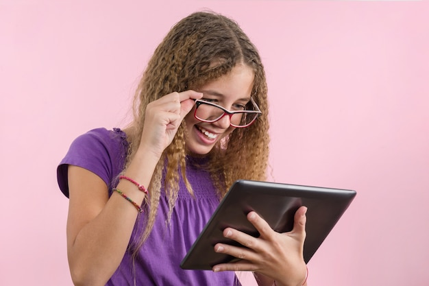 Teen school girl with glasses using digital tablet