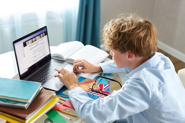Teen schoolboy prepares a presentation, writes a report