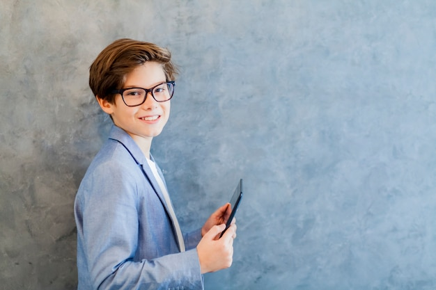 Teen schooler boy in eyeglasses holds tablet pc