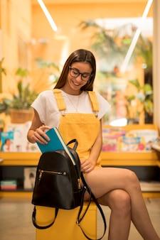 Teen schoolgirl placing book into backpack