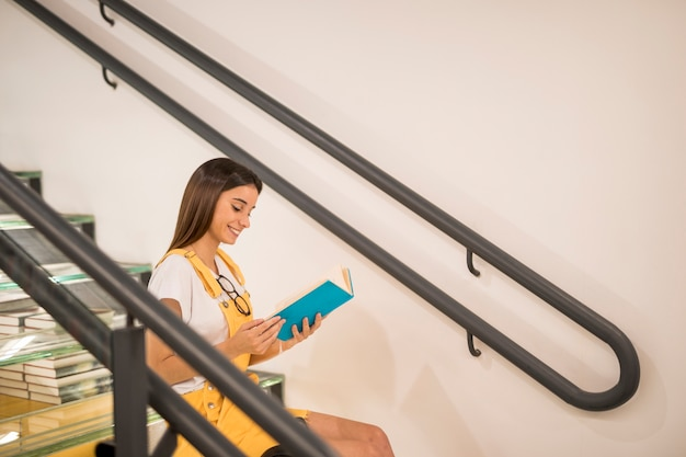 Teen schoolgirl reading book on stairs