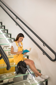 Teen schoolgirl sitting on stairs with book