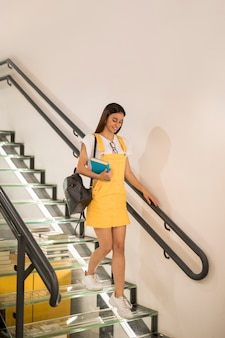 Teen schoolgirl walking downstairs with book