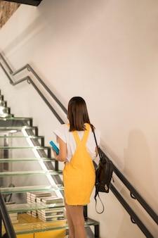 책으로 위층 걷는 십대 여학생