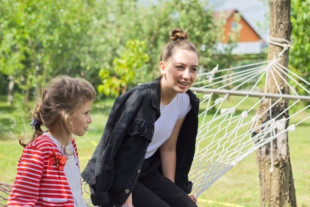 裏庭の庭でハンモックを楽しんでいる10代の姉妹の女の子と子供、幸せな笑いの女の子