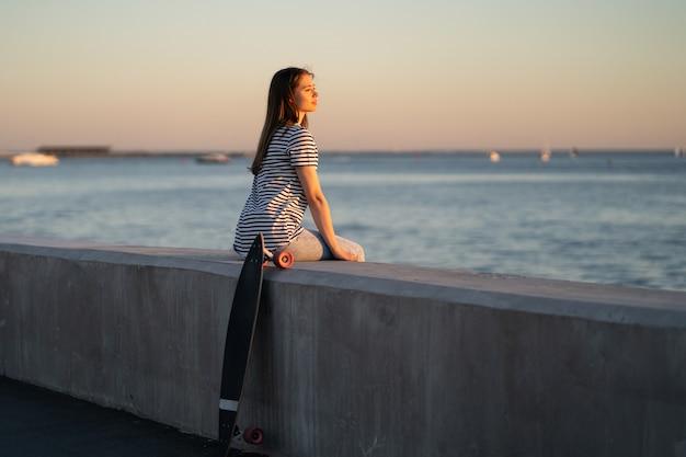Девушка-конькобежец на берегу моря на закате молодая женщина наслаждается летним вечером у реки или моря, глядя на воду