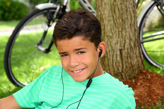 Teen smiling boy hearing music headphones grass
