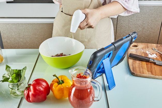 ティーンは、オンラインガイドを使用してサラダに油を振りかけ、自宅のキッチンで健康的な食事を準備しながら、タッチタブレットでデジタルレシピを確認します
