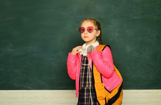십대 학생. 안경을 쓴 재미있는 여고생, 어린이 스튜디오 초상화. 교육 개념입니다. 학교 배낭과 헤드폰 어린 십 대 여 학생입니다.