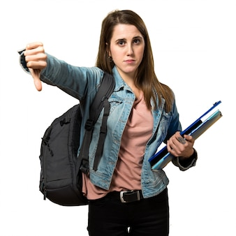 Teen student girl holding books and making bad signal