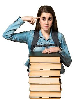 多くの本を持ち、狂ったジェスチャーをしているティーンの学生