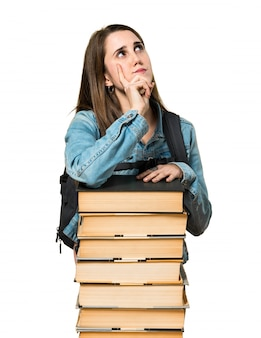 Teen student girl with a lot of books and thinking