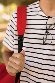 Teen student with glasses carrying backpack