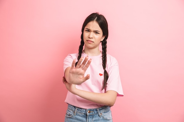 ピンクの壁に隔離された正面で停止ジェスチャーを拒否し、表示する2つの三つ編みを持つ10代の不幸な少女