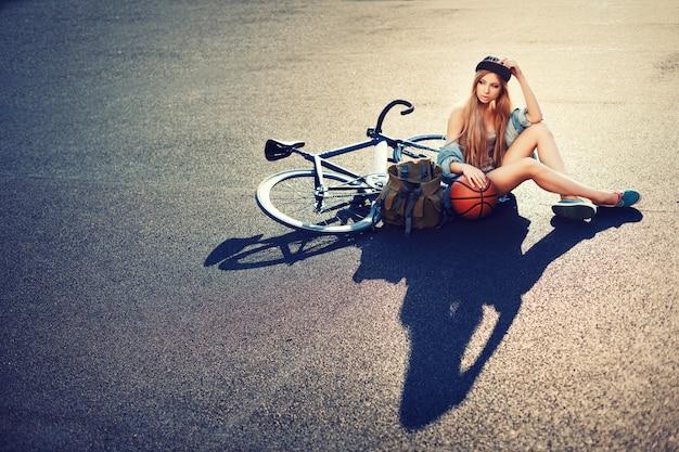 Teen wearing cap sitting with her bike