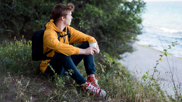 Teen with backpack sitting on ground in forest