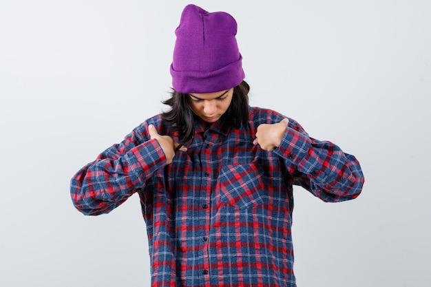 Teen donna in camicia a scacchi e berretto gesticolando isolato