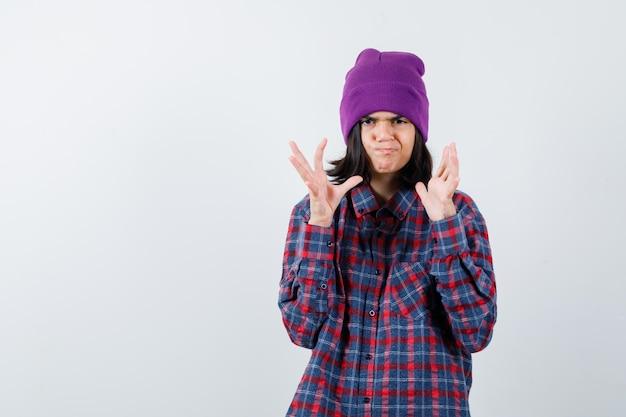 Donna teenager in camicia a scacchi e berretto che tiene le mani in modo perplesso e sembra infastidita