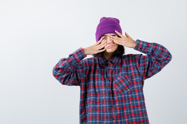 Teen woman in checkered shirt and beanie rubbing eyes with hands
