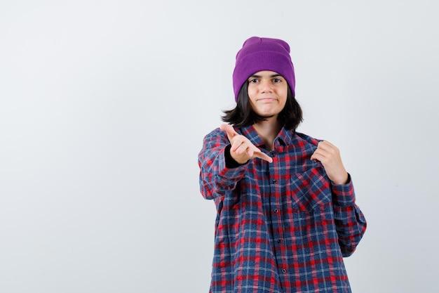 Donna teenager in camicia a scacchi e berretto che allunga la mano