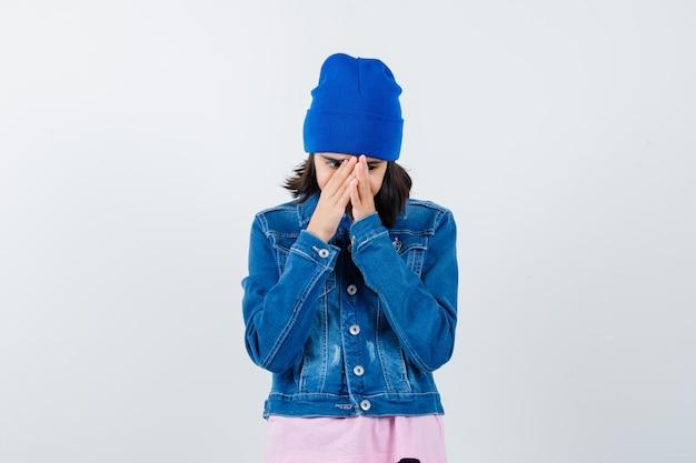 Teen donna stringendo le mani davanti al viso cercando ansiosa