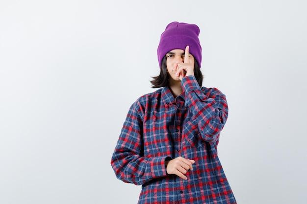 Молодая женщина закрывает глаз пальцем в клетчатой рубашке и шапочке, выглядит круто