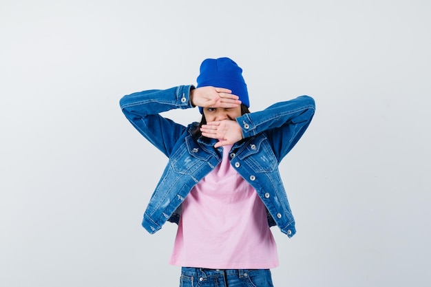 恥ずかしそうに見えるピンクのtシャツで手で顔を覆う10代の女性