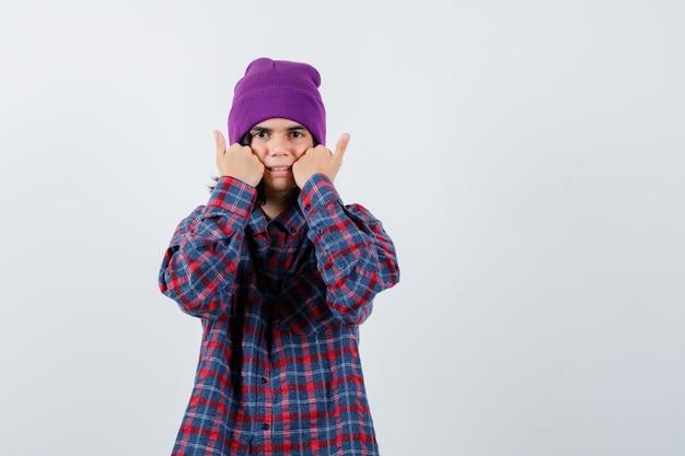 Молодая женщина, держащая кулаки по щекам в клетчатой рубашке и шапочке, осторожно смотрит