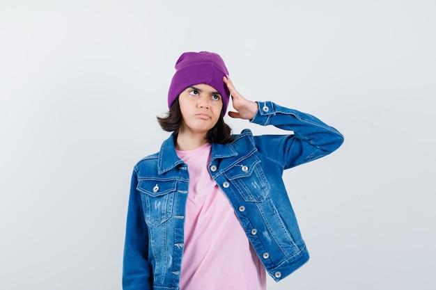 Teen donna che tiene la mano sulla testa in berretto giacca t-shirt che sembra pensierosa