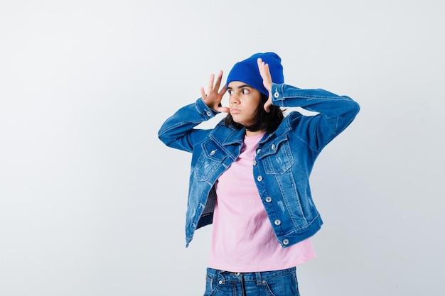 Подросток женщина, держащая руки возле головы в розовой футболке, джинсовой куртке, шапочке, выглядит испуганной