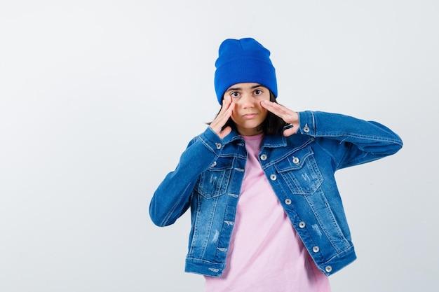 귀여운 찾고 분홍색 티셔츠 진 재킷 비니에 입 근처에 손을 잡고 십 대 여자