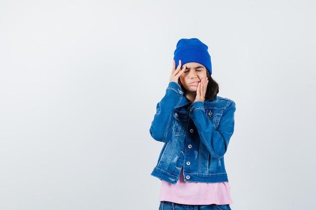 Молодая женщина, взявшись за руки на голове, морщась в розовой футболке, джинсовой куртке