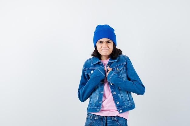 胸に手をつないでピンクのtシャツに顔をゆがめた10代の女性
